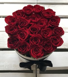 Czerwone żywe róże w średnim białym boxie