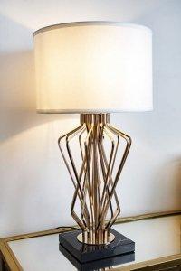 Złota lampa stojąca na marmurowej podstawie