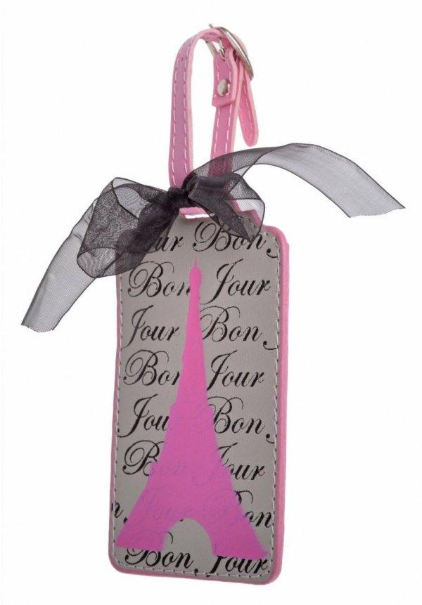 Zawieszka na bagaż z różową wieżą Eiffla, na pasku z klamerką przewiązanym czarną, tiulową wstążeczką. Z tyłu tabelka z możliwością wpisania danych adresowych. Wymiary bez paska: 13x7cm.